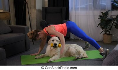 Fit sportwoman doing handstand exercise with pet