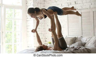 Fit sporty young couple practicing acro yoga together on bed