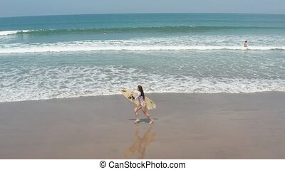 Fit surfer woman running on beach from ocean with surfboard....