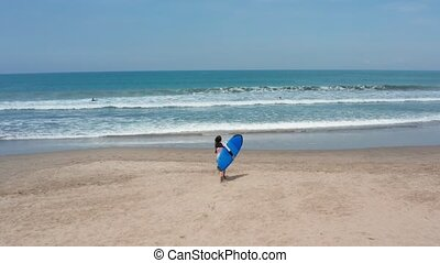 Fit surfer woman runs into the ocean with surfboard. Modern...