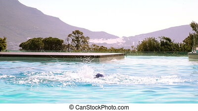 Fit swimmer doing butterfly stroke in outdoor pool on a...
