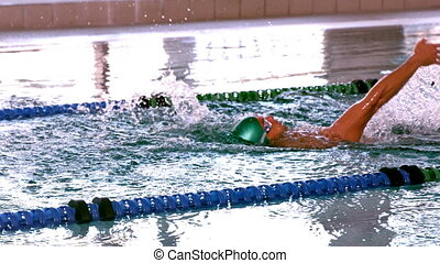 Fit swimmer doing the back stroke in the swimming pool in...