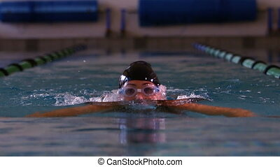 Fit swimmer doing the breast stroke in swimming pool in slow...