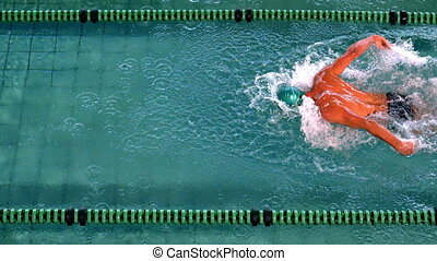 Fit swimmer doing the butterfly stroke in the swimming pool in slow motion