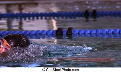 Fit swimmer doing the front stroke in swimming pool in slow...