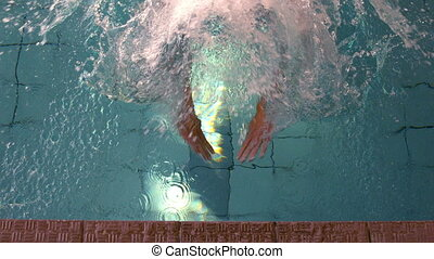 Fit swimmer swimming to the edge of the pool in slow motion