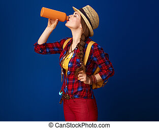 fit tourist woman isolated on blue background drinking water