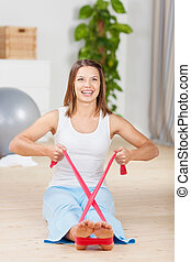 Fit woman athlete doing exercise with Theraband at home