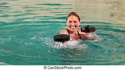 Fit woman doing aqua aerobics in th