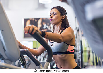 Fit woman doing cardio in an elliptical trainer in a gym.