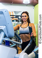 Fit woman doing exercise on a elliptical trainer.