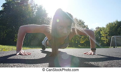 Fit woman doing full plank core exercise fitness training working out outdoors. Push up