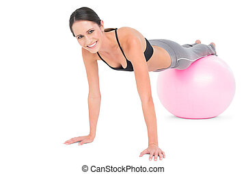 Fit woman doing push ups on fitness ball - Full length...