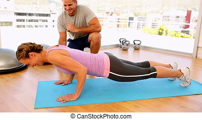 Fit woman doing push ups with her t