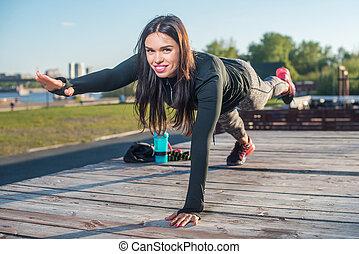 Fit woman doing raised leg plank yoga pilates exercises...