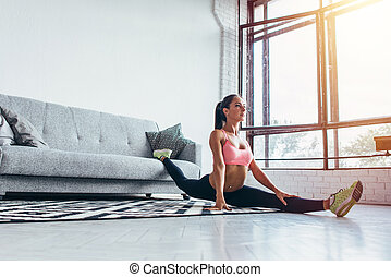 Fit woman doing split exercising at home Flexibility, stretching, fitness