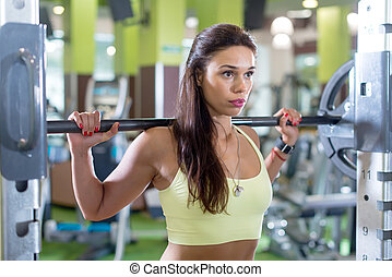 Fit woman doing squats with a barbell in Smith machine.
