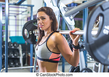 Fit woman doing squats with the barbell Smith machine in the gym.