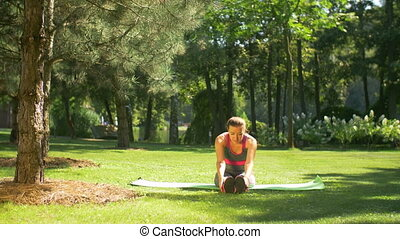 Fit woman doing stretching pilates exercises outdoors