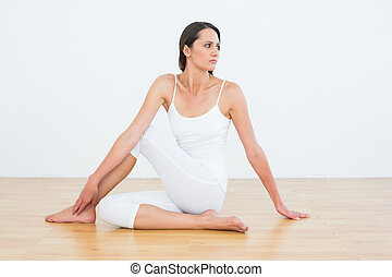 Fit woman doing the half spinal twist pose in fitness studio...