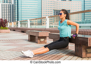 Fit woman doing triceps bench dips exercise while listening...
