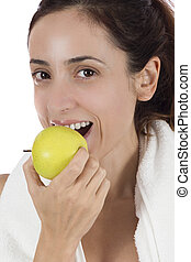 Fit woman eating apple after work out