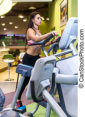 Fit woman exercising at fitness gym aerobics elliptical walker trainer workout.