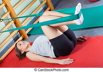Fit woman exercising in fitness studio with elastic band