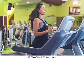 Fit woman exercising on treadmill in gym.