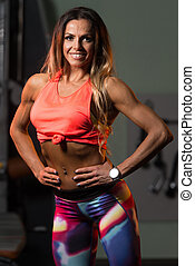 Fit Woman Flexing Muscles In Gym