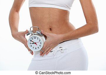 fit woman holding a clock