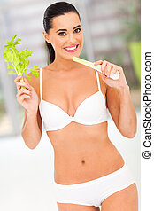 fit woman holding celery