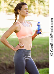 Fit woman holding water bottle in the park