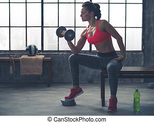 Fit woman in profile on bench lifting weights in loft gym -...
