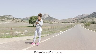Fit woman in sportswear using phone