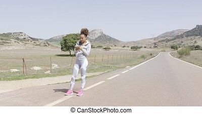 Fit woman in sportswear using phone