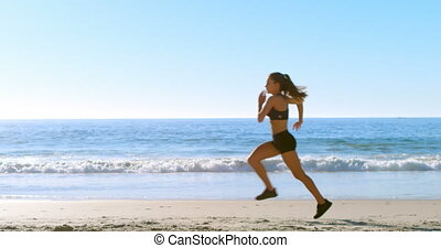 Fit woman jogging in the beach 4k - Fit woman jogging in the...