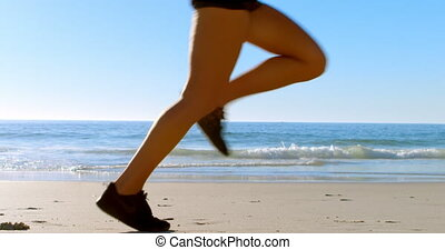 Fit woman jogging in the beach on a sunny day 4k