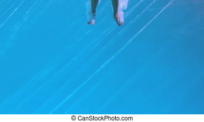 Fit woman jumping into swimming pool in slow motion