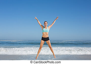 Fit woman jumping on the beach with arms out on a sunny day