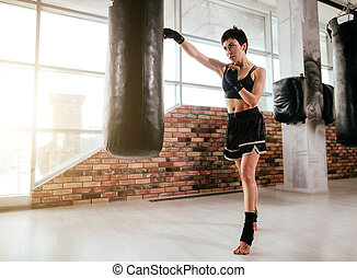 fit woman learning muay thai boxing at gym