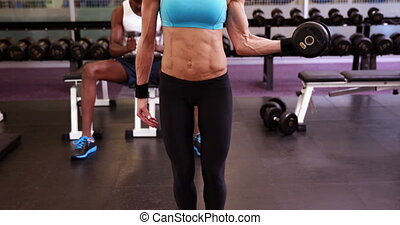 Fit woman lifting dumbbells at cros