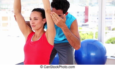 Fit woman lifting dumbbells with trainer at the gym
