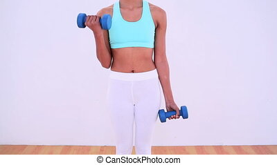 Fit woman lifting hand weights at home in bright room
