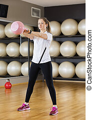 Fit Woman Lifting Kettlebell In Health Club