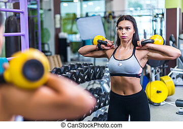Fit woman looking at mirror, exercising with kettlebell in gym