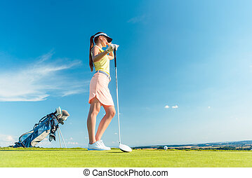 Fit woman looking at the horizon on the green grass of a golf course