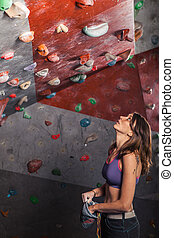 Fit woman looking up at rock climbing wall