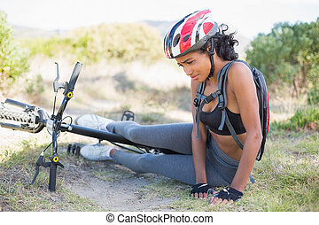 Fit woman lying on ground after bik
