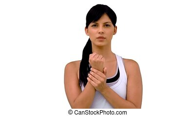 Fit woman massaging her wrist on white background in slow...